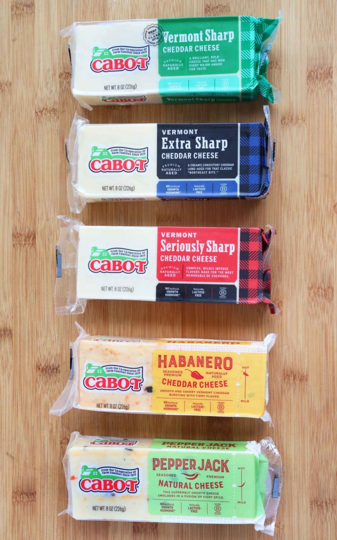 5 varieties of packaged Cabot Cheddar on a cutting board
