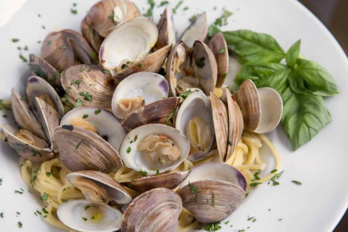 overhead view of clams and spaghetti in a white bowl