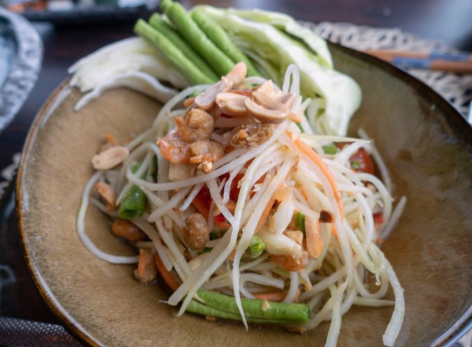 green papaya salad with peanuts in a brown bowl