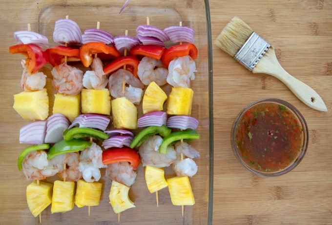 shrimp, pineapple, red and green peppers and red onions on skewers with a bowl of chili sauce and a brush