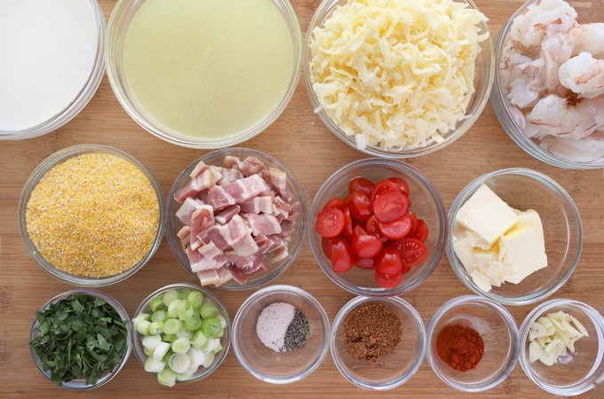 ingredients to make cheesy grits and shrimp in glass bowls on wooden cutting board