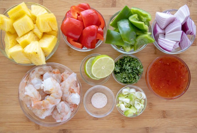 ingredients to make grilled shrimp and pineapple skewers in glass bowls on a wooden cutting board
