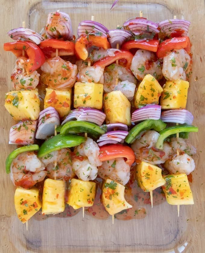 shrimp and pineapple skewers in a glass baking dish