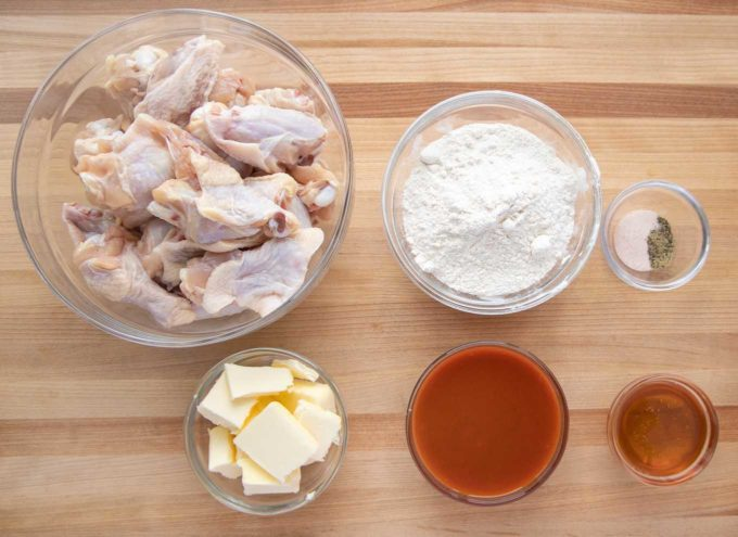 overhead view of ingredients to make buffalo chicken wings in glass bowls on a wooden cutting board