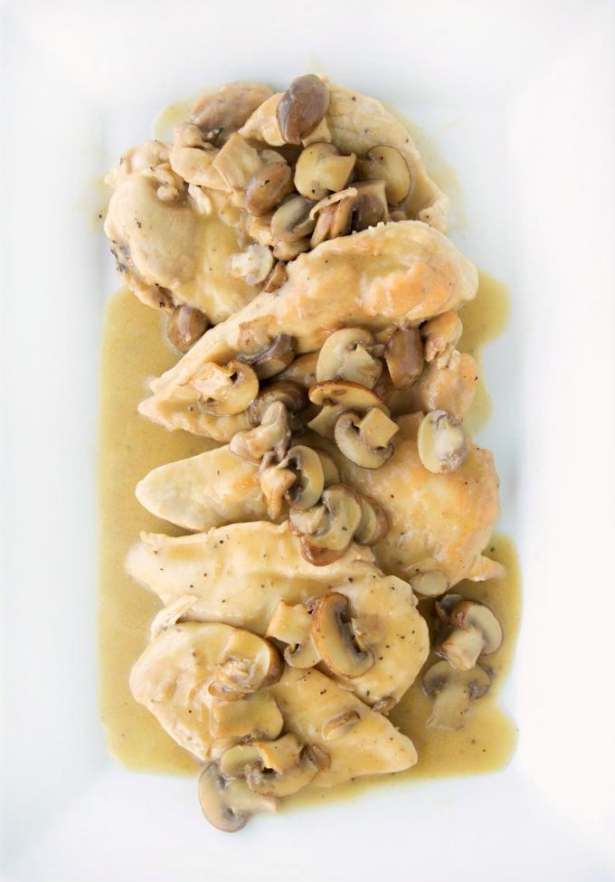 overhead shot of chicken marsala with mushrooms on a white platter