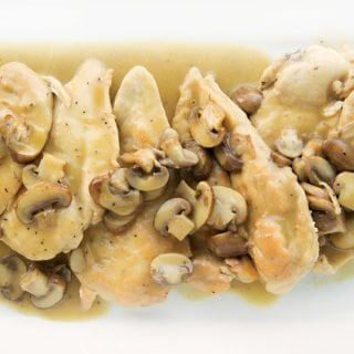 overhead view of chicken marsala on a white platter