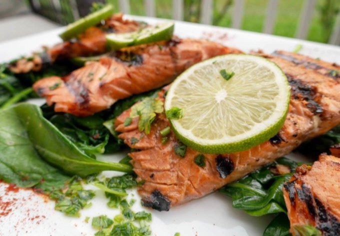 marinated grilled salmon un a bed of spinach with slices of lime on top