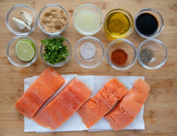 ingredients for marinade in glass bowls with salmon fillets on white paper