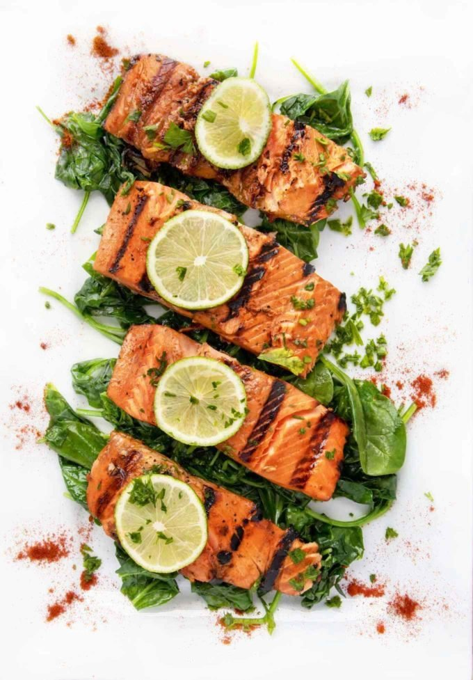overhead view of marinated grilled salmon with lime slices on top sitting on a bed of wilted spinach on a white platter