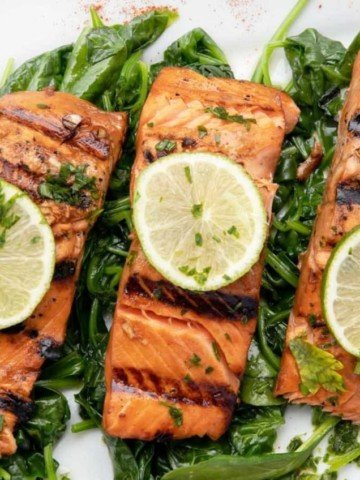 overhead view of marinated grilled salmon un a bed of spinach with slices of lime on top