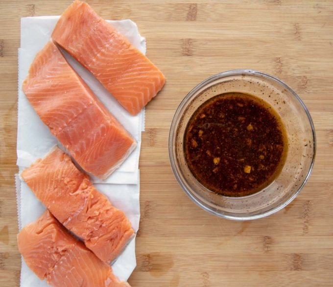 4 salmon filets on white paper next to a glass bowl of marinade