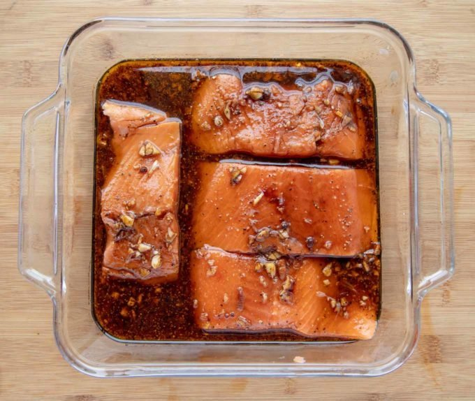 4 salmon filets marinating in a glass baking dish
