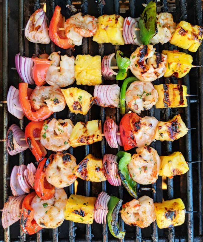 overhead shot of shrimp and pineapple skewers cooking on the grill.