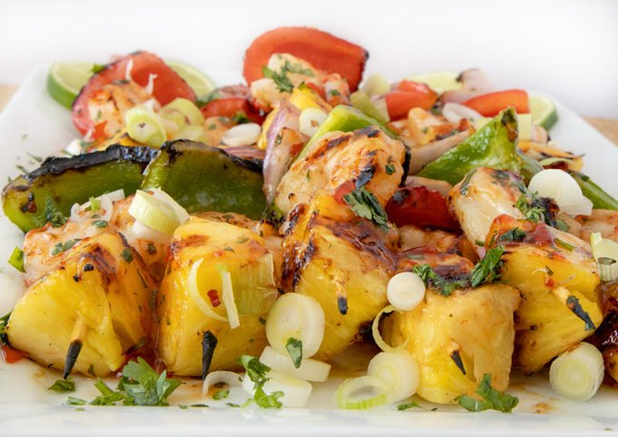 front view of grilled shrimp and pineapple skewers on a white platter