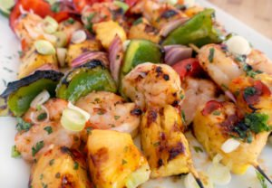 close up of grilled shrimp and pineapple skewers on white platter
