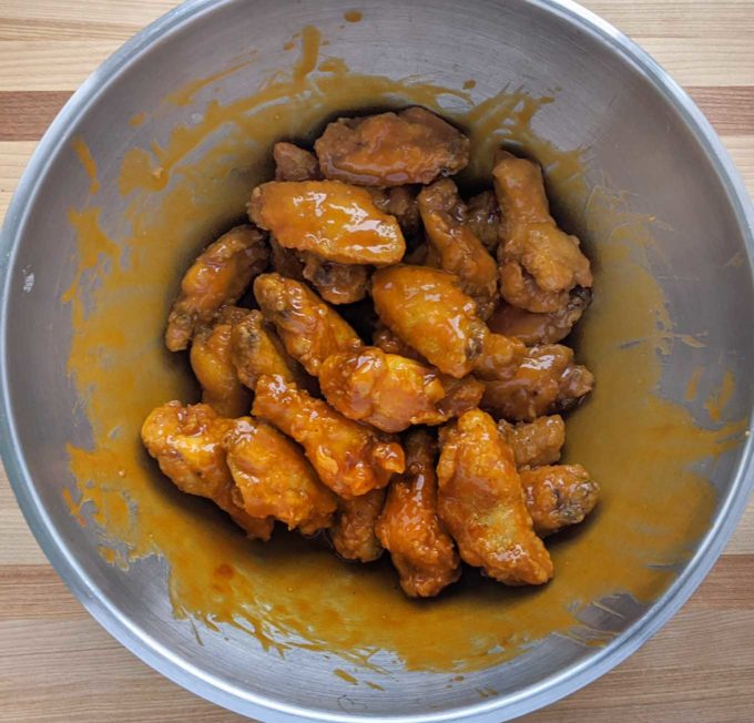 overhead view of fried chicken wings coated in buffalo sauce in a large stainless steel bowl
