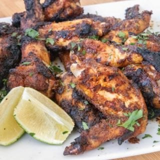 white platter of grilled and charred dry rub chicken wings with chopped parsley sprinkled on top