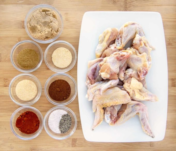 small glass bowls of spices and a white platter of raw chicken wings on a wooden cutting board
