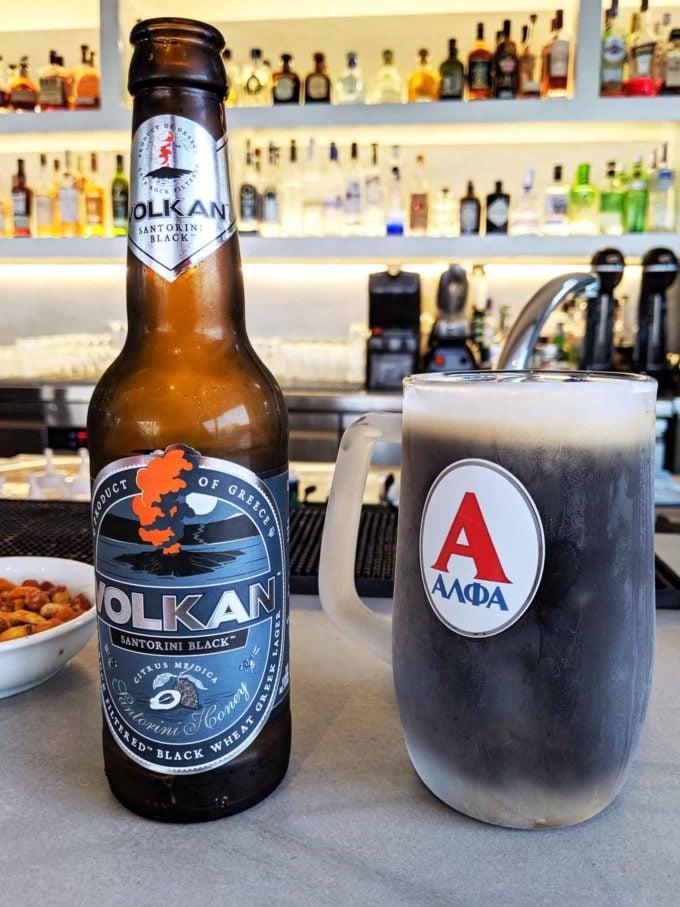 bottle of Volkan Black beer next to full mug of beer