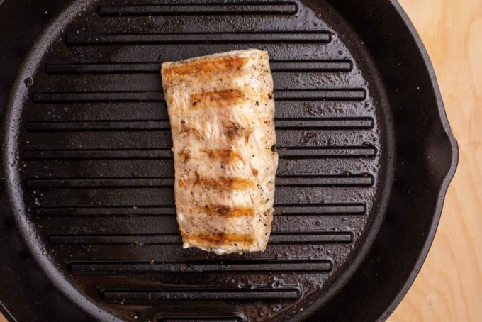 mahi-mahi in a grill pan with one side grilled with grill marks