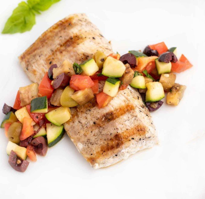 grilled mahi mahi with caponata on a white plate