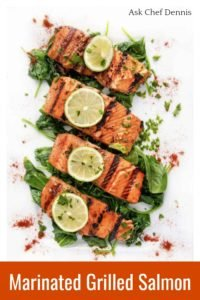 4 grilled salmon filets on a bed of wilted spinach on a white platter