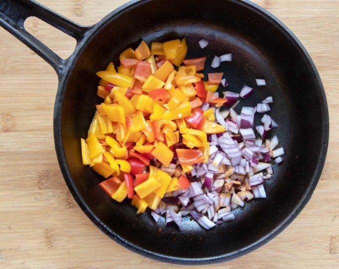 diced raw tri color peppers and diced raw red onions in a cast iron skillet