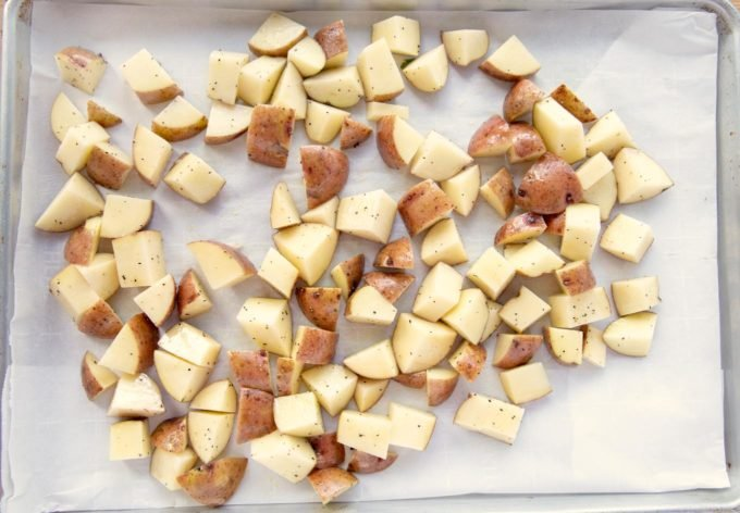 diced, oiled and seasoned red potatoes on a sheet pan