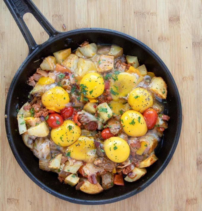 cast iron skillet filled with potatoes, meats and veggies topped with whole raw eggs