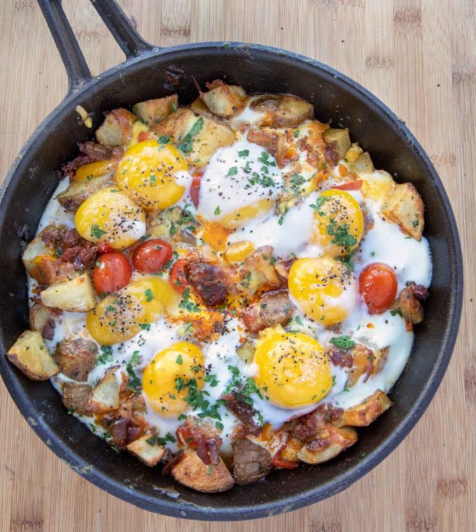 cast iron cheesy skillet breakfast with sunny side up eggs on top