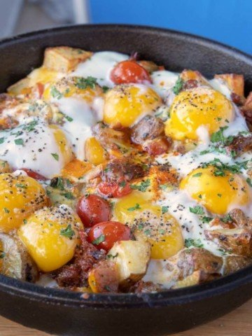 cast iron skillet breakfast with sunny side up eggs on top