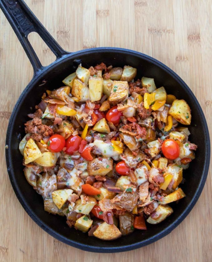 cast iron skillet filled with potatoes, sausage, bacon, onions, tomatoes, peppers and melted cheddar
