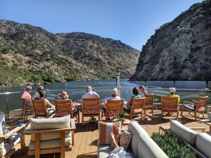 people sitting in deck chairs on the end of the Viking Helgrim looking at the Douro Valley in Portugal