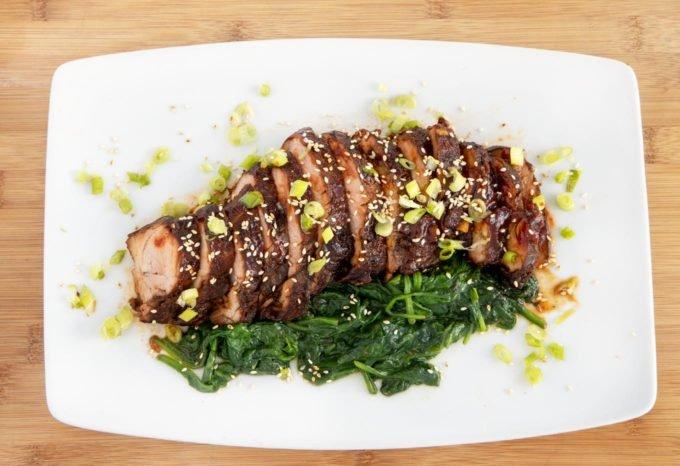 White Platter with sliced pork tenderloin and spinach.
