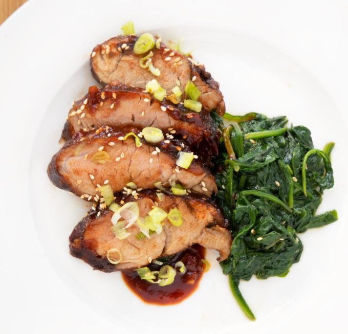 Korean Pork Barbecue and spinach on a white plate