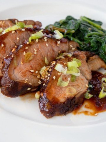 slices of Korean Pork Barbecue on a white plate sprinkled with toasted sesame seeds and sliced scallions