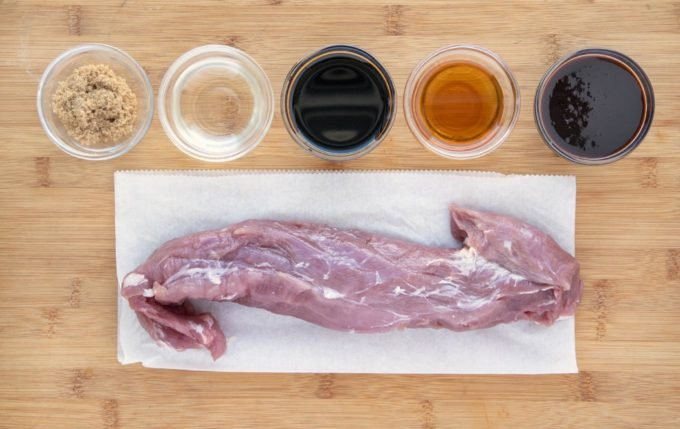 ingredients for the marinade in glass bowls and pork tenderloin on a white plate