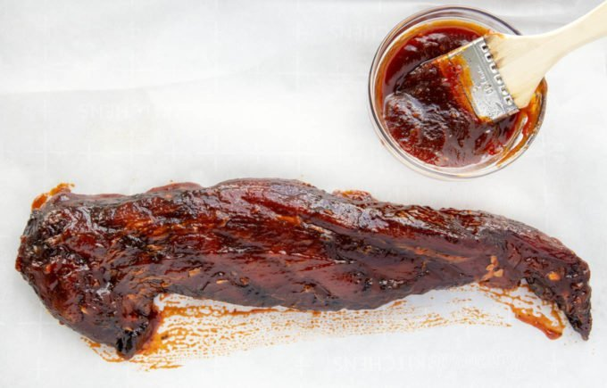 Pork Tenderloin brushed with Korean Barbecue sauce, bowl of bbq sauce and brush on the side