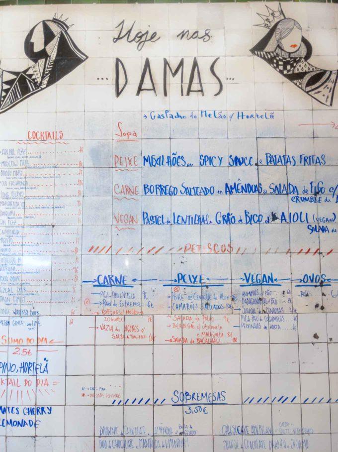 Menu handwritten on a tile wall at Damas in Lisbon