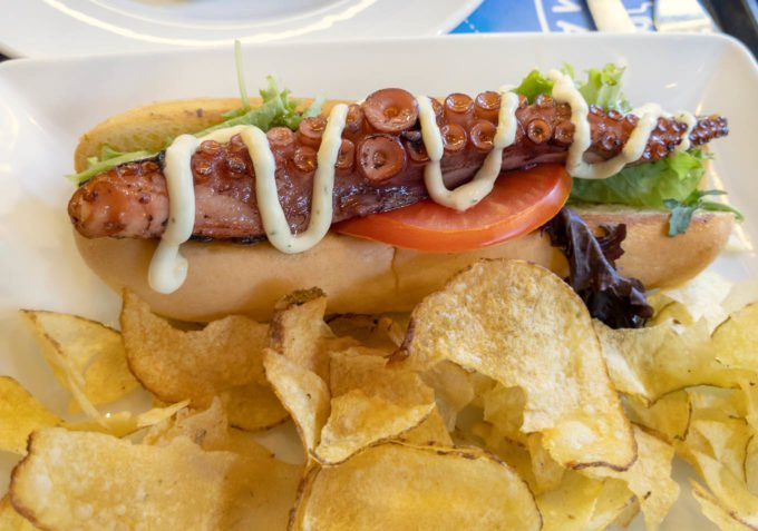 octopus tentacle on a hot dog roll with potato chips on the side