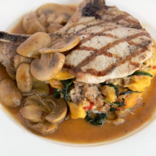 stuffed pork chop with mushroom gravy on a white plate