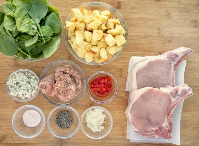 ingredients to make stuffed pork chops on a wooden cutting board