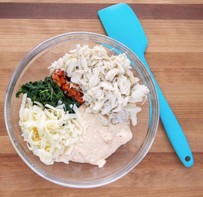 ingredients to make crabmeat and cheese stuffing in a glass bowl with a blue rubber spatula next to it