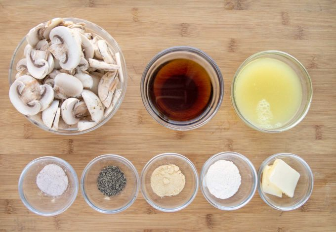 ingredients to make mushroom marsala sauce in glass bowls on a wooden cutting board
