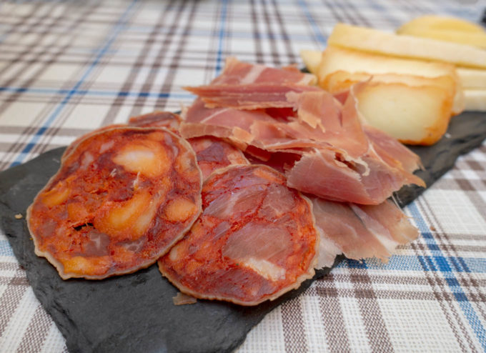 cured meats and cheese on a rectangular piece of slate on a checkered tablecloth