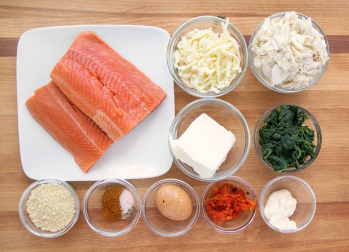 ingredients to make stuffed salmon in bowl on a wooden cutting board
