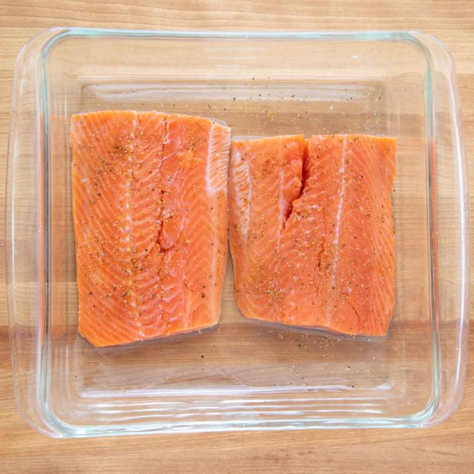 2 salmon fillets seasoned with sea salt and black pepper in a glass baking dish