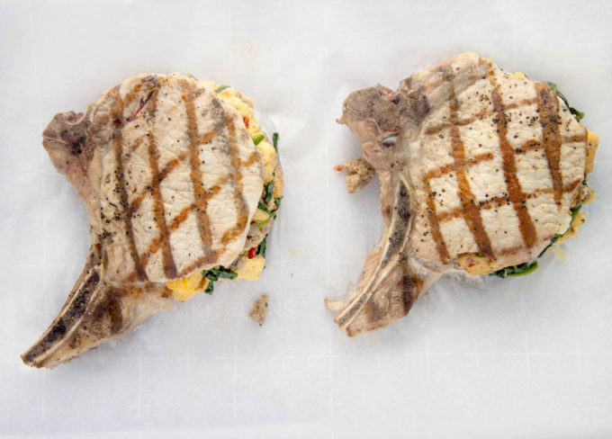 2 stuffed pork chops with grill marks on a white cutting board