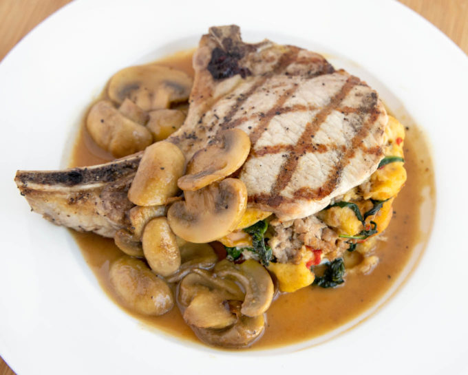 stuffed pork chop with grill marks on a white plate with mushroom gravy