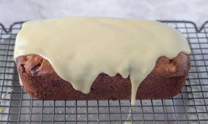 white chocolate ganache covering the top of the cannoli pound cake on a wire rack
